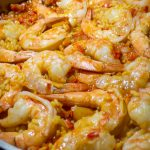 paella in large pan with shrimp laying on top just cooked p
