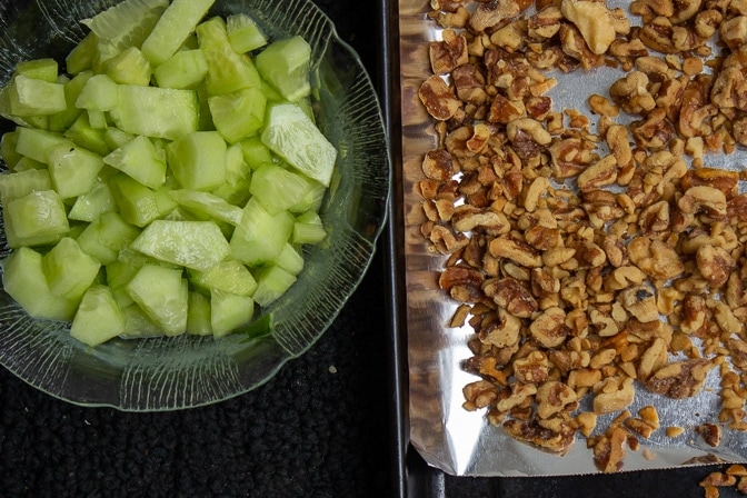 bowl of chopped cucumber and pan of roasted walnuts