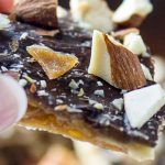 hand holding piece of caramel and chocolate coated matzo with nuts p2