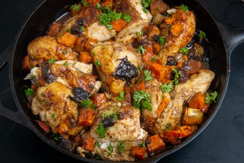 cut up Moroccan roast chicken with sweet potatoes in a skillet f