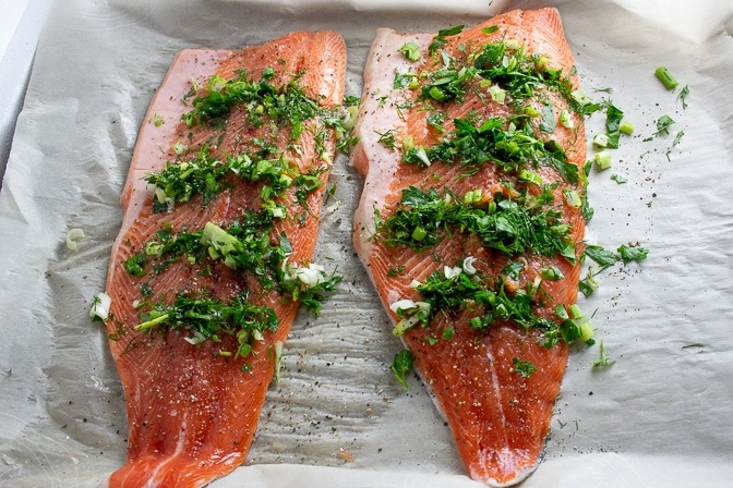 two Trout fillets stuffed with herbs on pan ready for baking