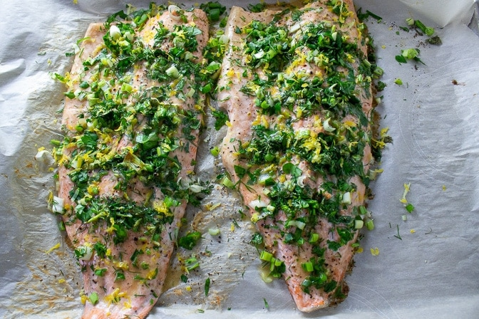 2 Lemon Herb Baked Trout fillets on baking pan with extra lemon and herbs