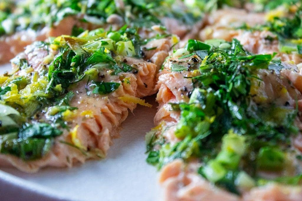 two Lemon Herb Baked Trout fillets cut into portions sitting on a plate