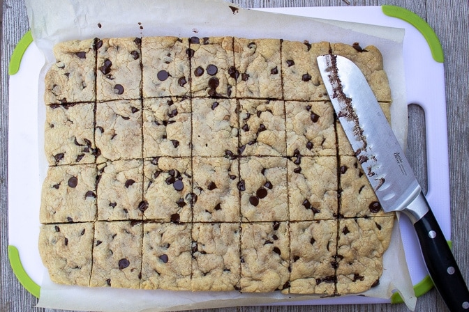 cooled chocolate chip cookie bars cut into squares in pan