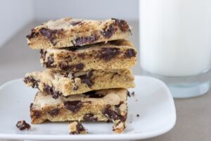 four chocolate chip cookie bars stacked on plate with milk beside it