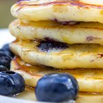 stack of lemon blueberry pancakes in plate with syrup on top and fresh blueberries p
