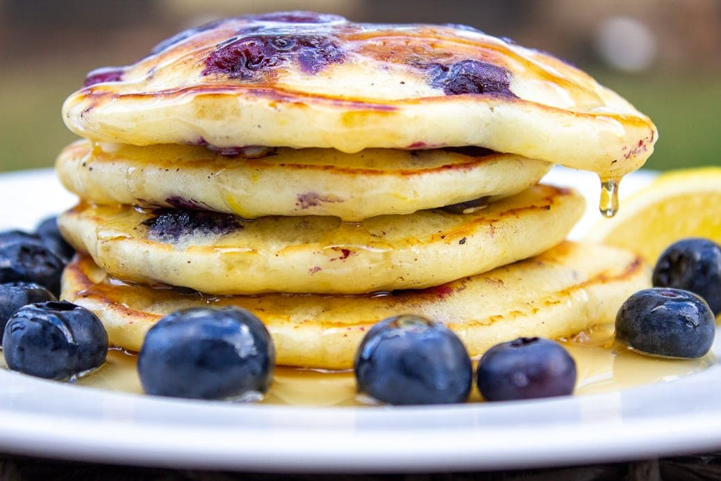stack of lemon blueberry pancakes in plate with syrup on top and fresh blueberries