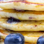 stack of lemon blueberry pancakes in plate with syrup on top and fresh blueberries p1