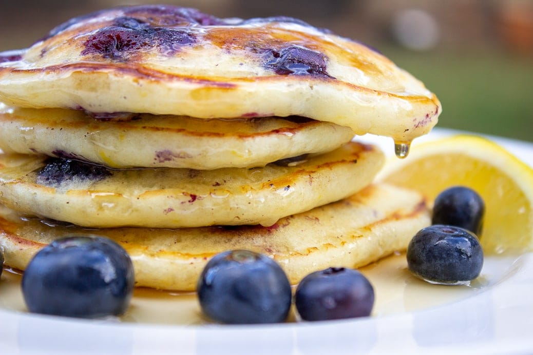 stack of lemon blueberry pancakes in plate with syrup on top and fresh blueberries 1