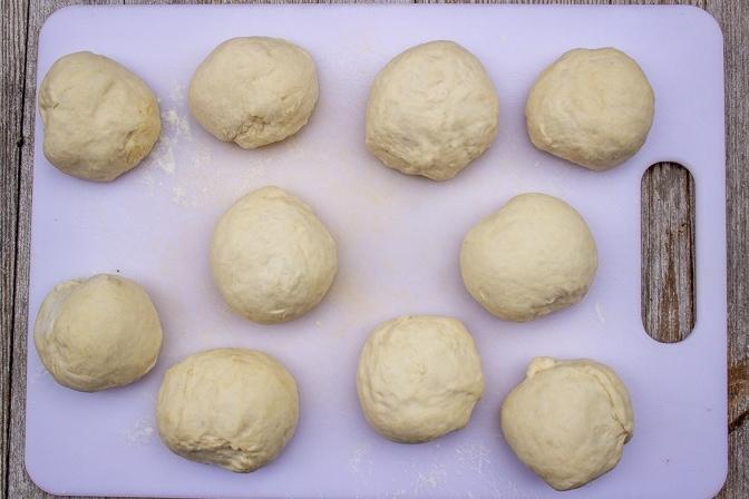 balls of english muffin dough on cutting board