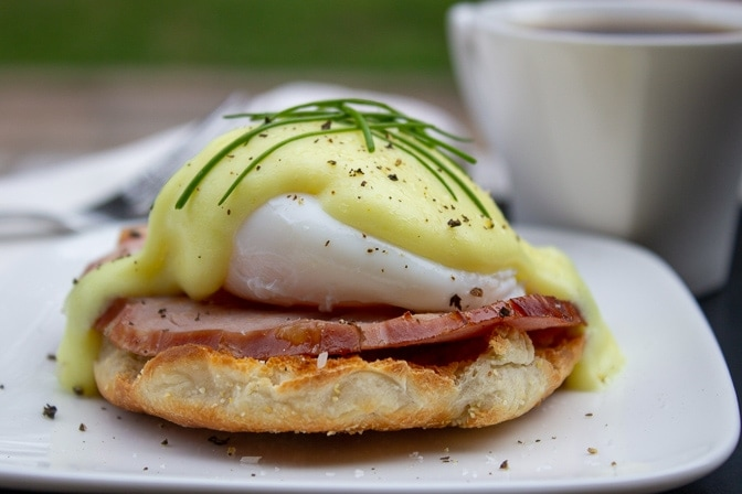 eggs benedict on half an English muffin on plate