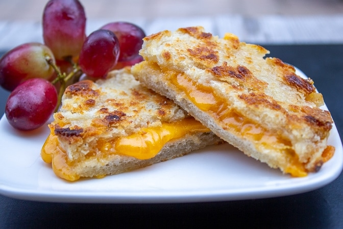 grilled cheese on an english muffin on a plate with grapes