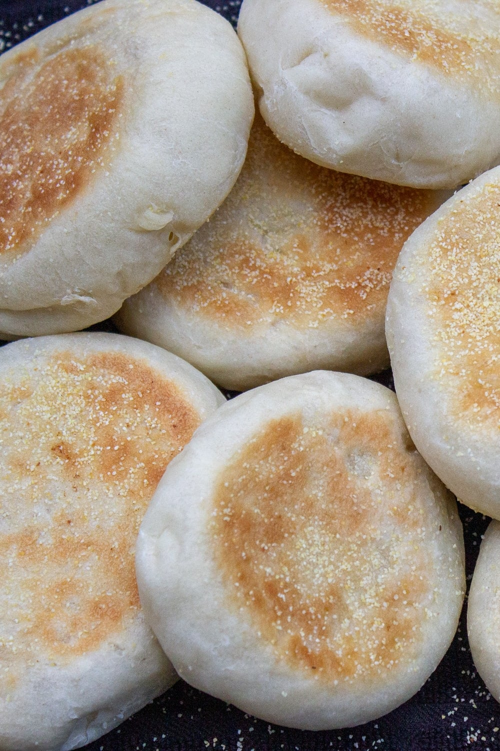 homemade English muffins laying on a black tea towel p