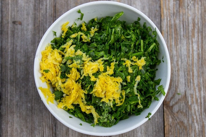 chopped herbs and grated lemon zest in a bowl