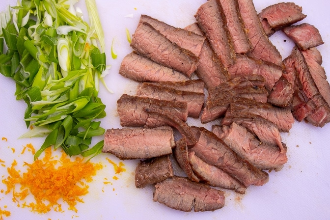 beef sliced, cut of green onion and orange zest on cutting board