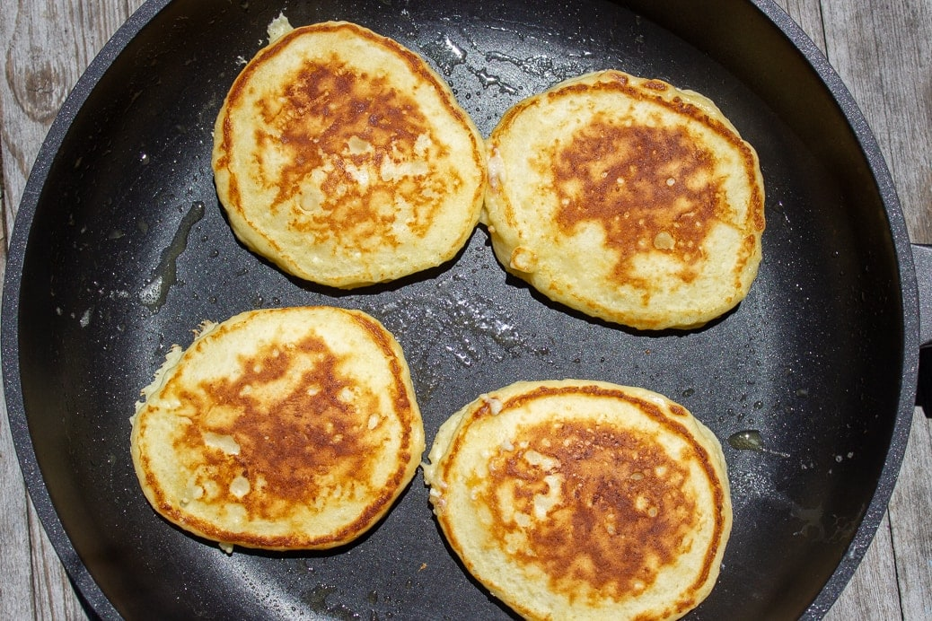 4 pancakes cooking in pan