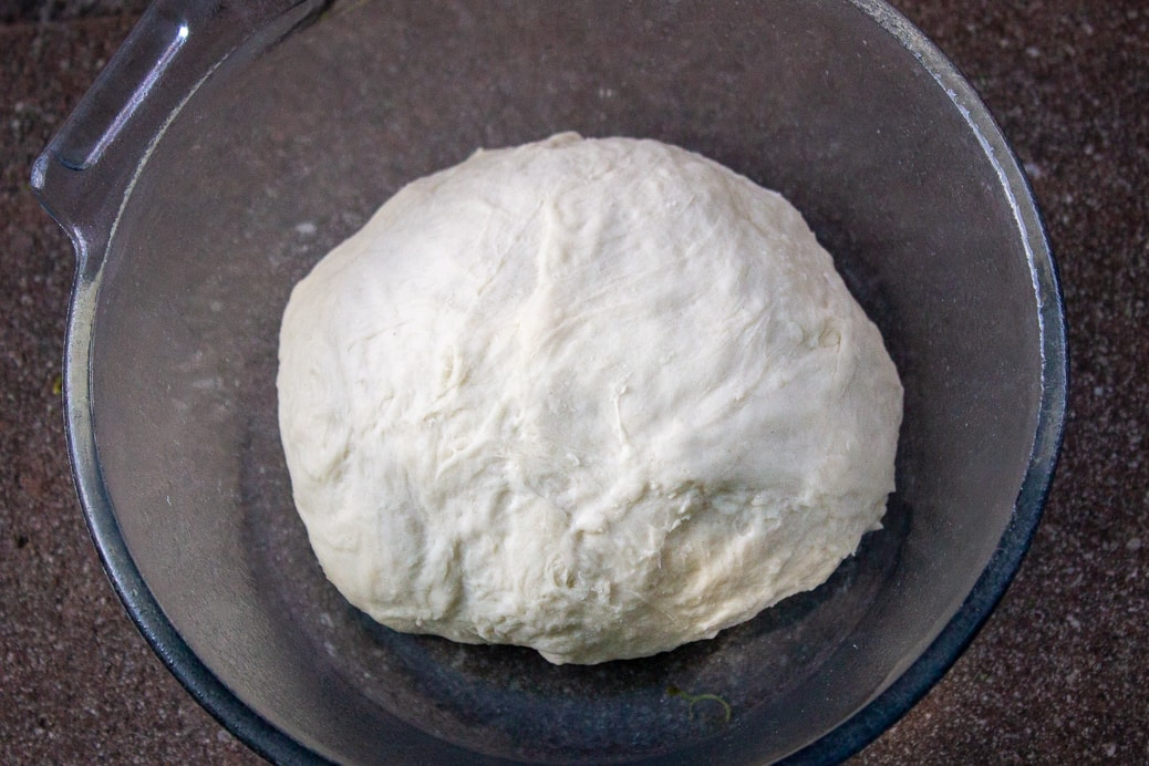 rolled piece of dough in bowl ready to rise
