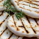 several grilled naan on cutting board p