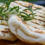 two naan on cutting board with sprig of rosemary p