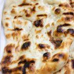 one naan bread on cutting board p
