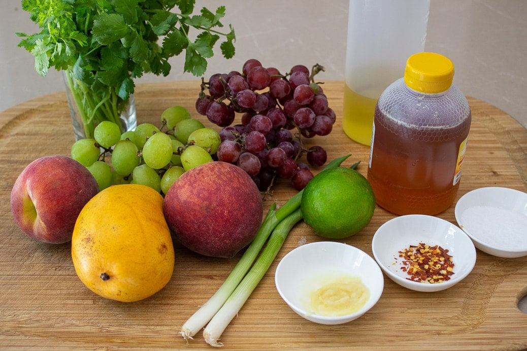 grapes, peaches, mango, oil, honey, ginger, chili flakes, cilantro, lime, green onion