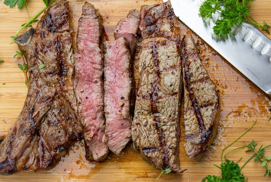 grilled rib steak sliced on cutting board