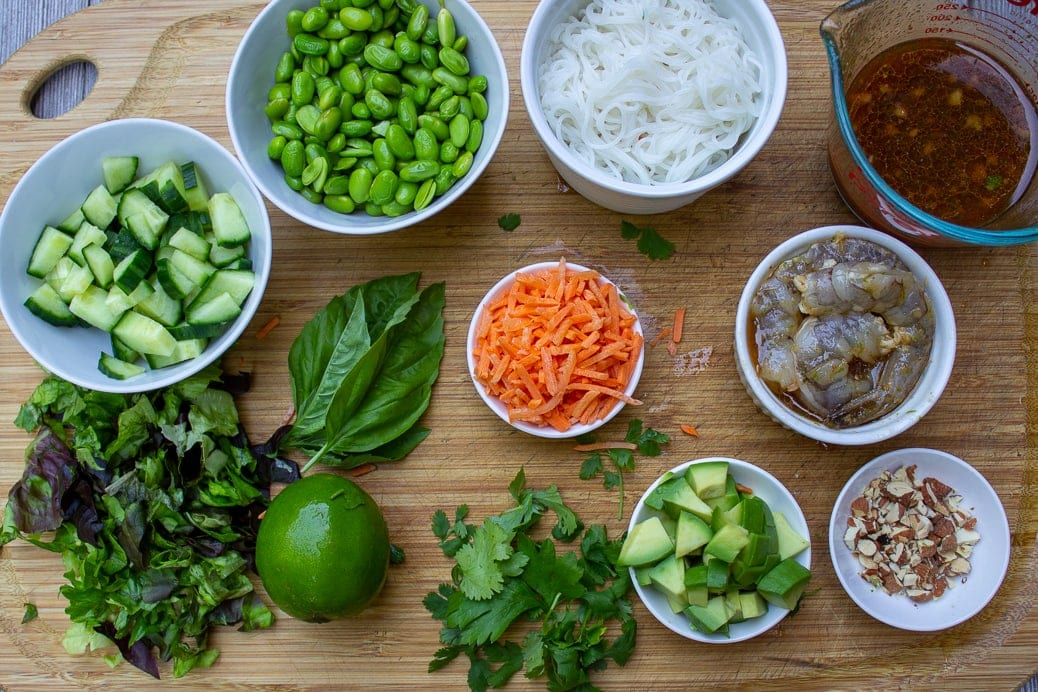 cooked noodles, edamame beans cooked, lettuce, lime, basil, cilantro, chopped cucumber, shredded carrots, chopped avocado, chopped nuts, raw shrimp, dressing in cup - all on cutting board