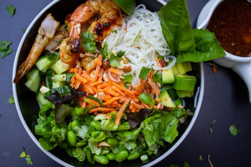 bowl with noodles, veggies, shrimp, garnish on mat