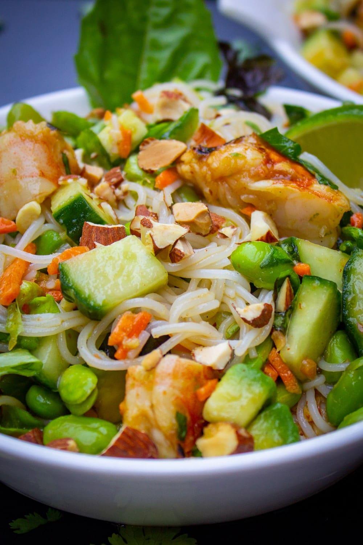 close up of mixed noodles, veggies, shrimp, garnish and dressing in bowl p1