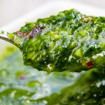 spoonful of herb sauce held over dish of sauce p