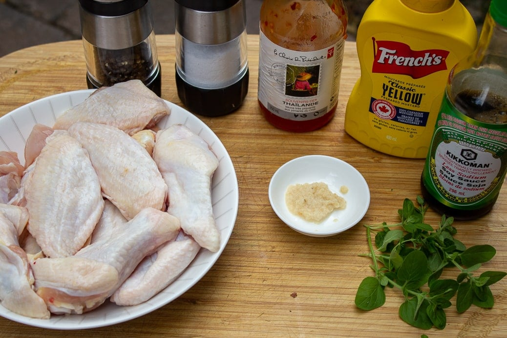 split chicken wings in bowl, salt, pepper, Thai sweet chili sauce, mustard, garlic, oregano, soy