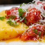 plate of polenta topped with tomato herb salad p3