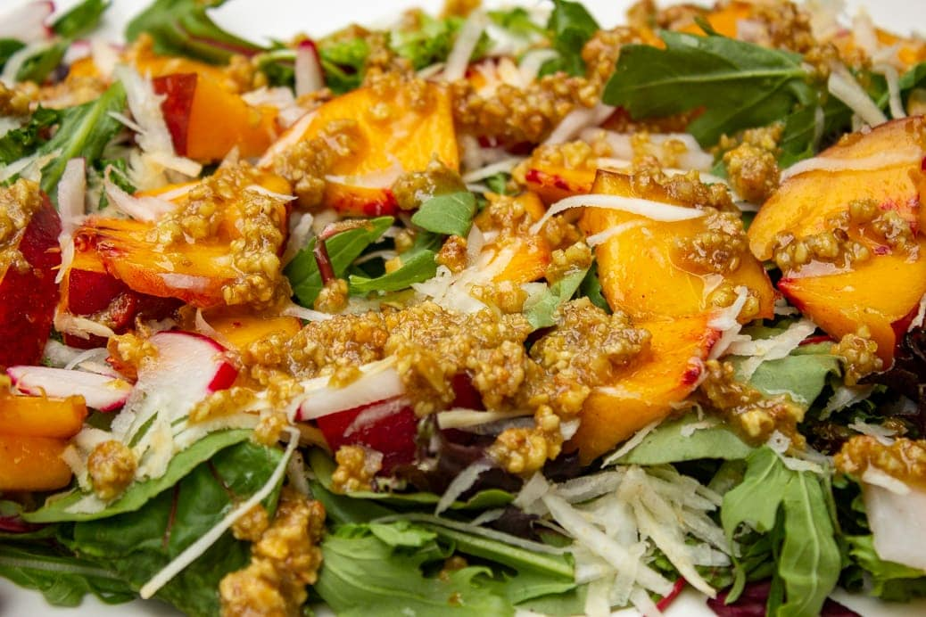 close up of peach salad with walnut dressing