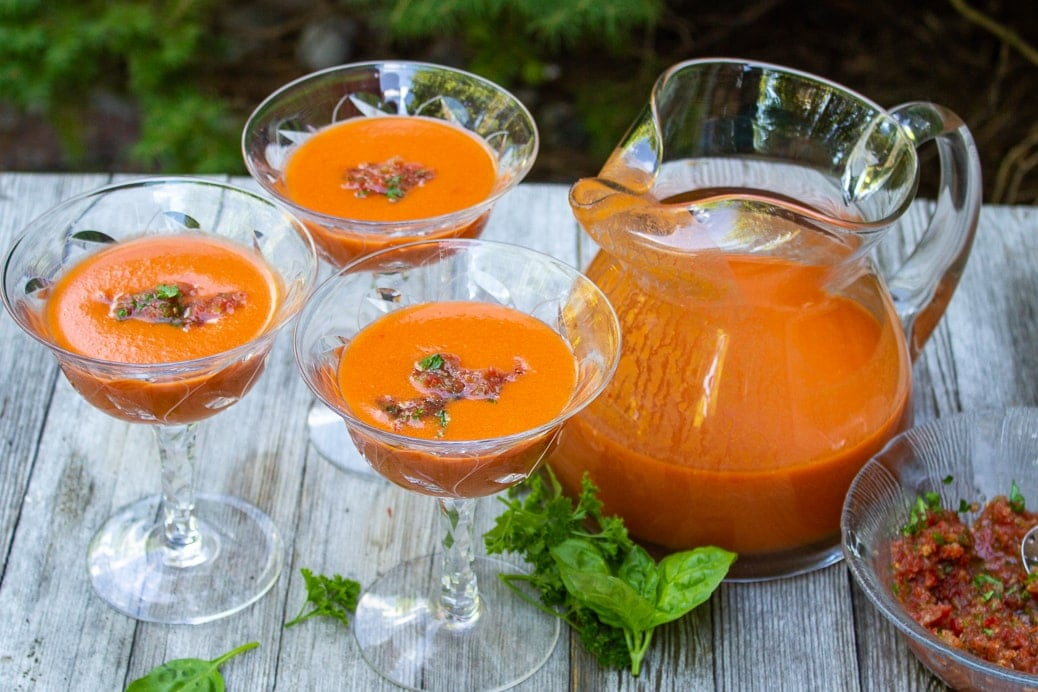martini glasses with gazpacho on wooden table with pitcher of gazpacho