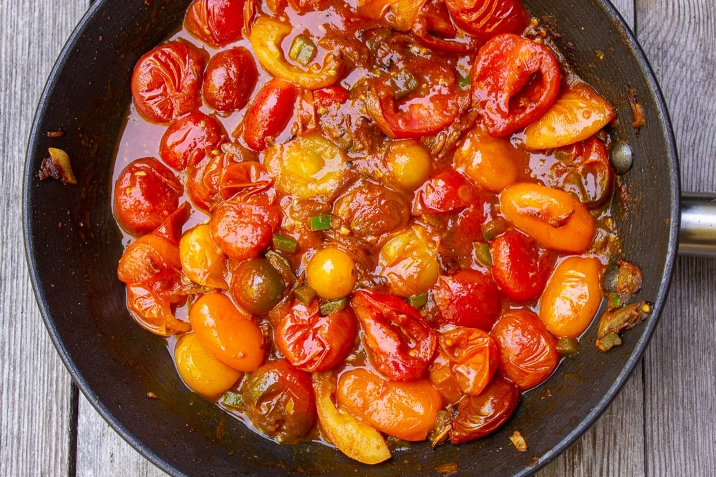 partially cooked cherry tomato sauce in pan