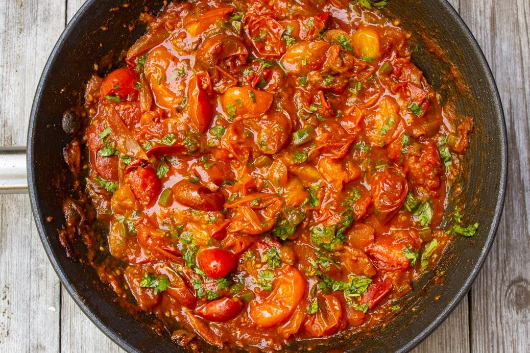 cherry tomato sauce in pan with cilantro