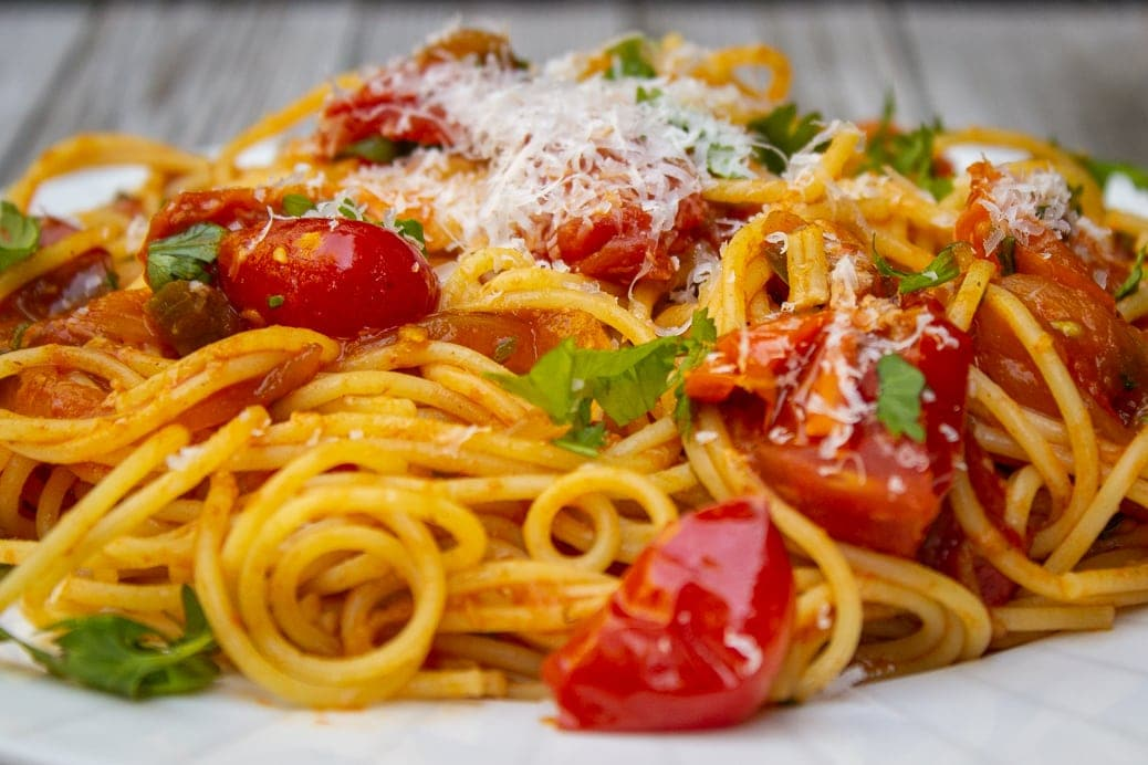 cherry tomato sauce mixed with spaghetti on plate
