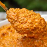 spoonful of roasted red pepper sauce over bowl p