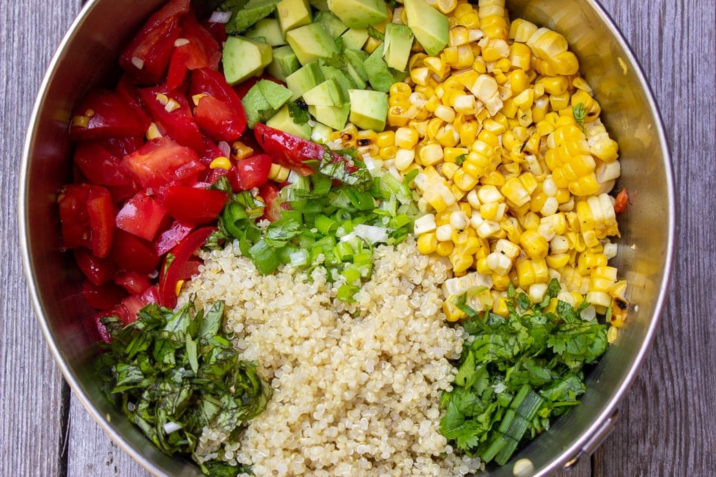 Corn, chopped tomatoes, chopped avocado, chopped herbs and quinoa in bowl