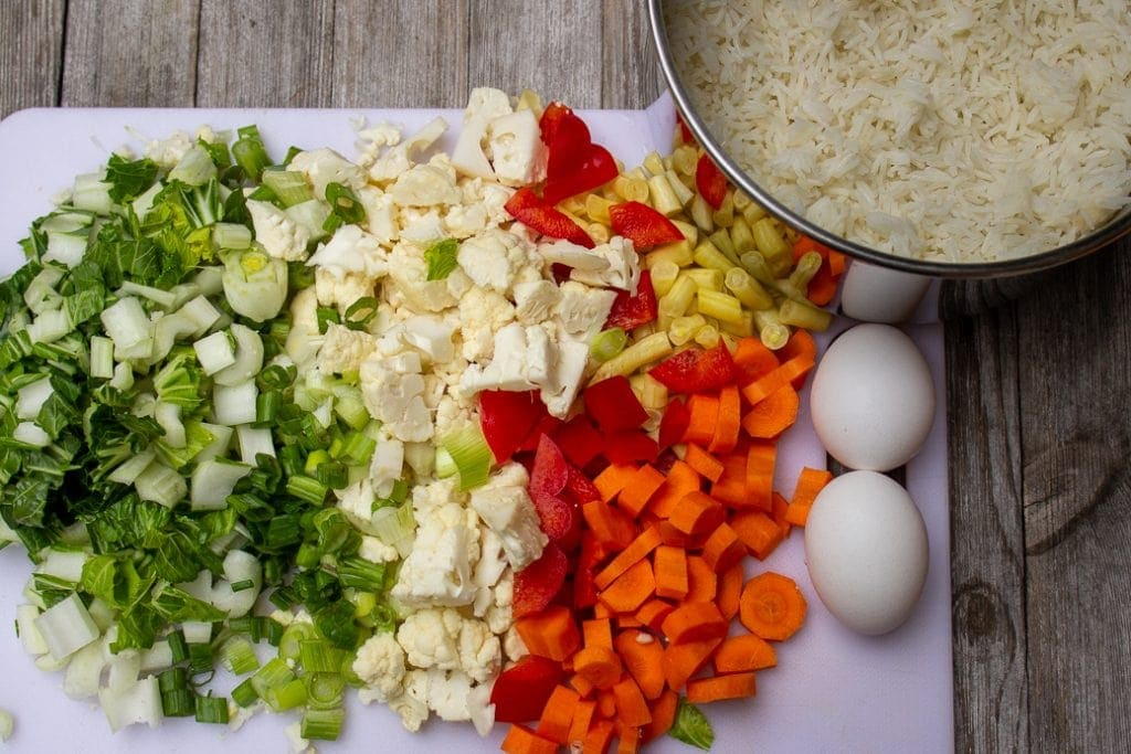 chopped boy choy, green onion, peppers, celery, cauliflower, eggs, cooked rice