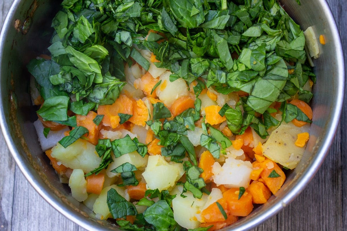 cooked root vegetables and chopped spinach in pot