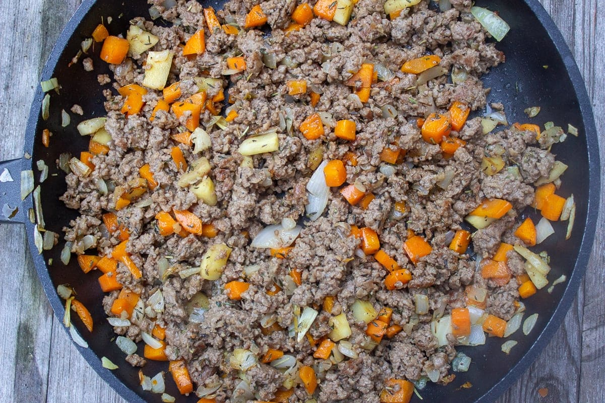 plant based beef added to sauteed veggies in skillet
