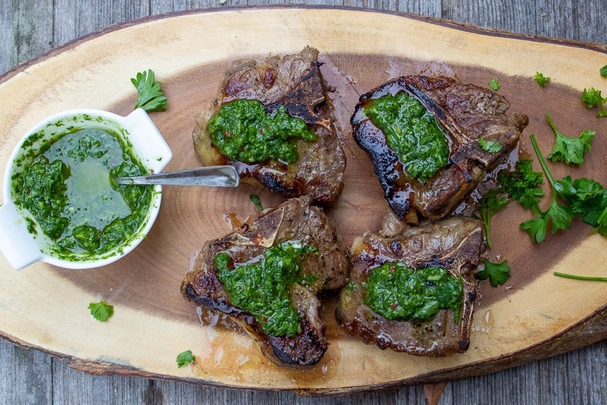 seared chops on serving board drizzled with chimichurri