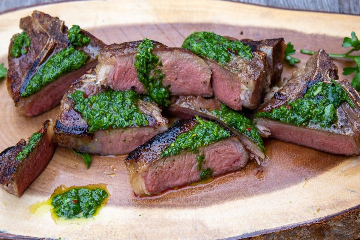 sliced lamb chops piled on serving board