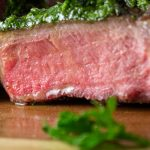 sliced lamb chops drizzled with chimichurri on serving board p