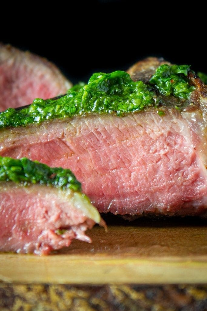 sliced lamb chops drizzled with chimichurri on serving board p1