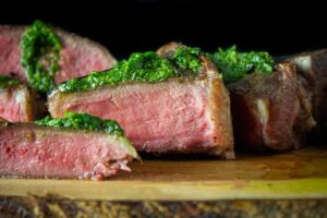 sliced lamb chops with chimichurri on top sitting on board
