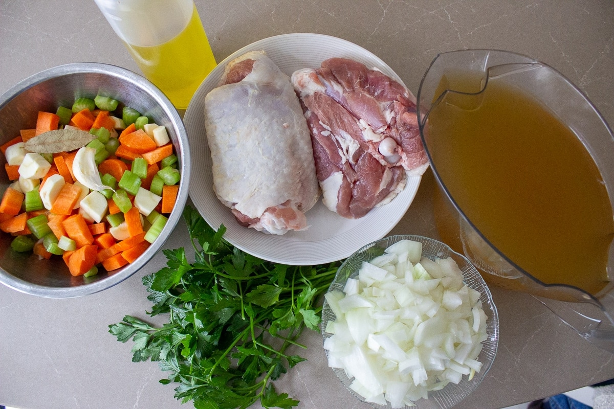 turkey thighs, chopped carrots, celery, parsnips, onions, parsley, bay leaf, garlic, broth, oil