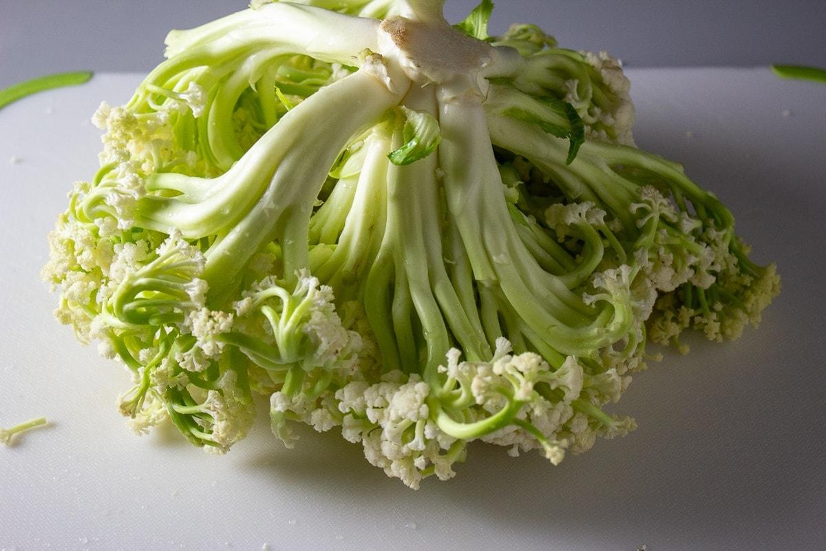 raw whole baby cauliflower on cutting board