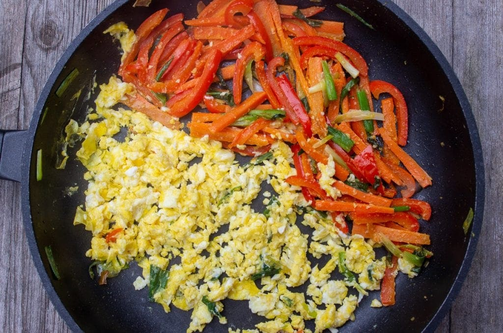 scrambled egg in pan with peppers and onion